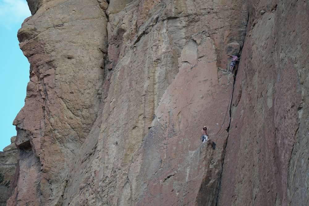 person climbing on brown rocky mountain during daytime