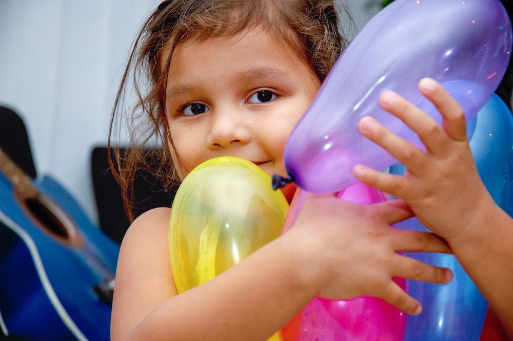 girl holding yellow and purple balloon