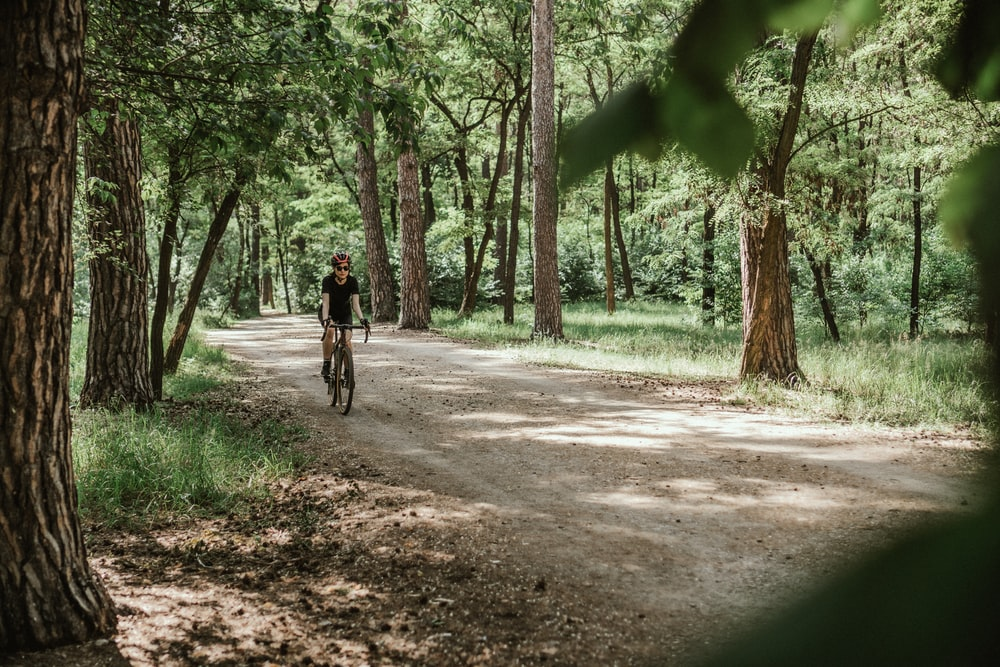 man in black jacket riding bicycle on dirt road between green trees during daytime