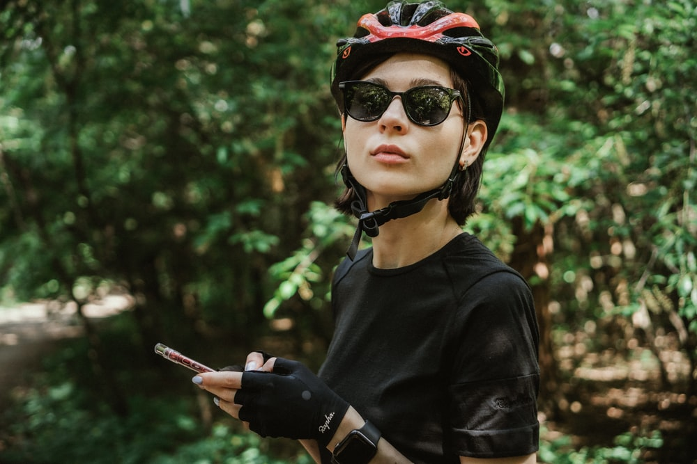 woman in black crew neck shirt wearing black sunglasses and red and black cap holding smartphone