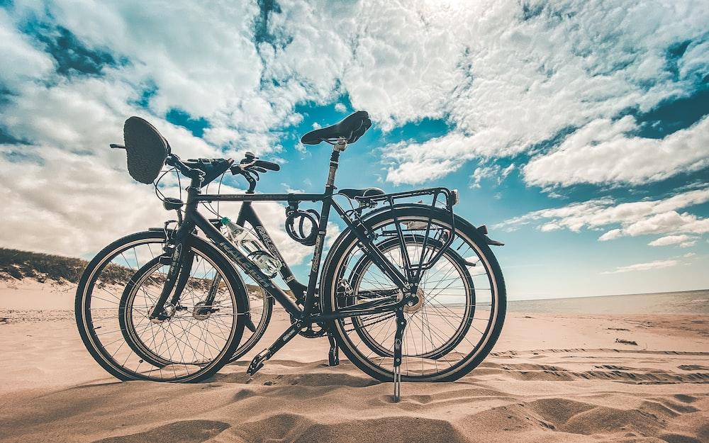 black commuter bike on brown sand under blue sky during daytime