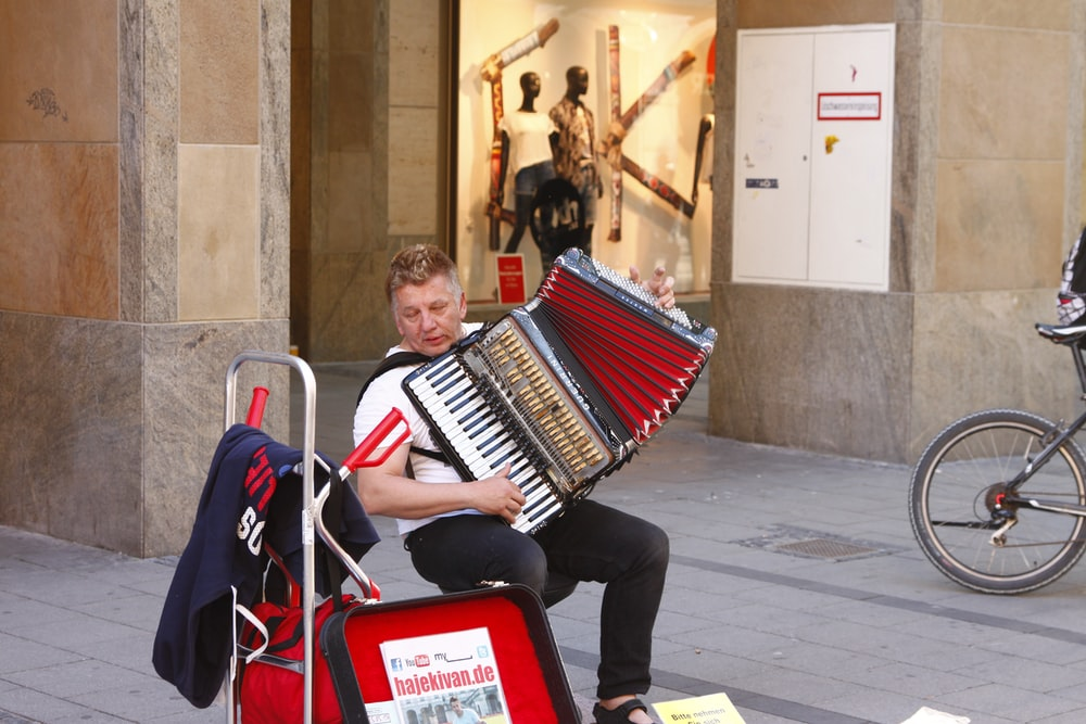 man in black jacket playing red and white piano