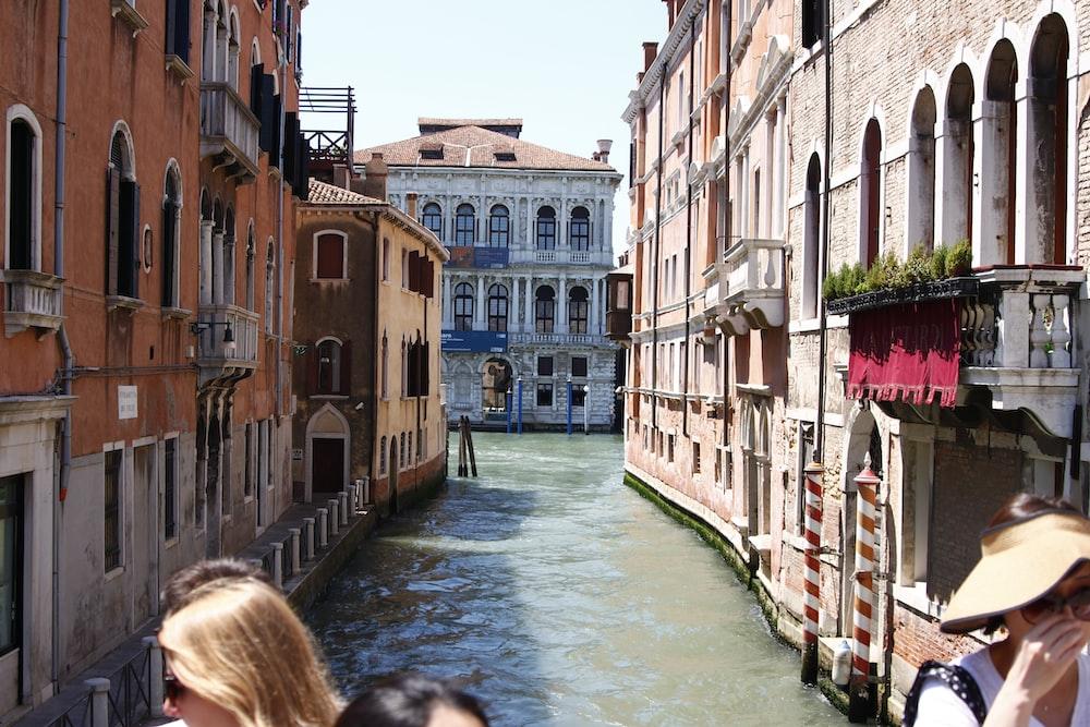 people walking on river between concrete buildings during daytime