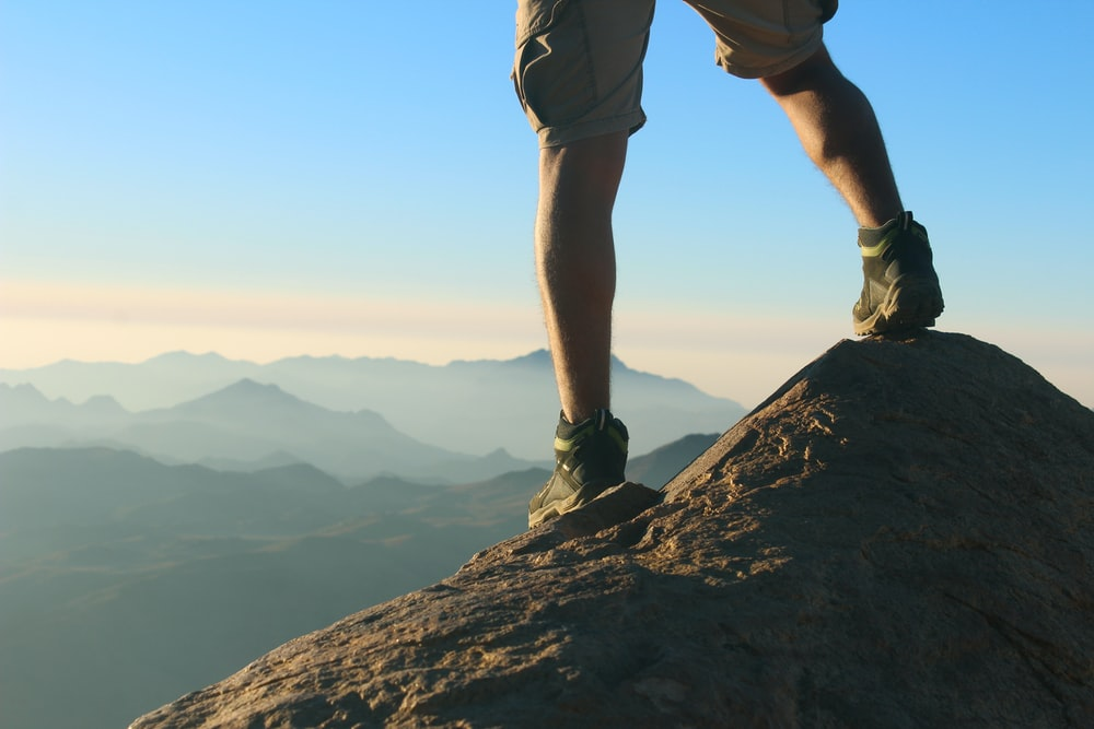 man in green shorts standing on rock formation during daytime