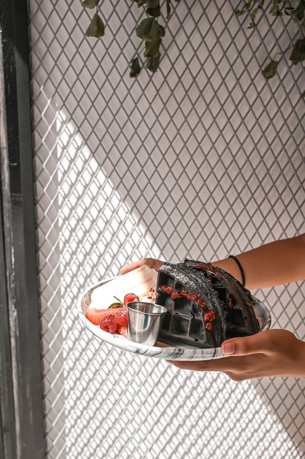 person holding clear glass bowl with red liquid