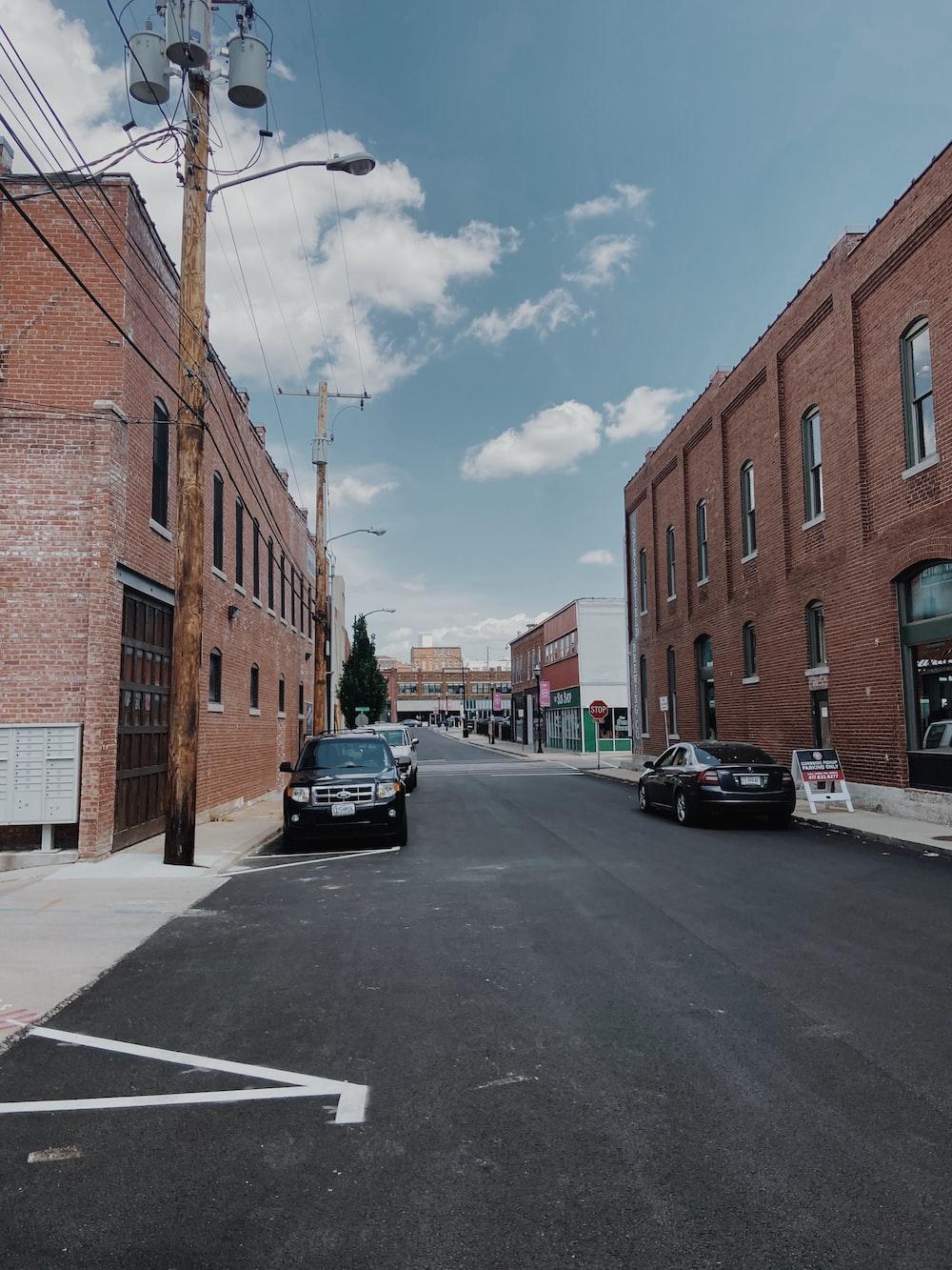 black car parked beside brown concrete building during daytime