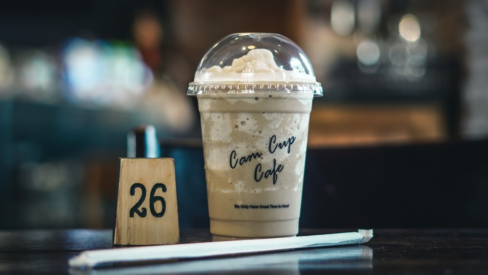 white and brown disposable cup with lid and straw