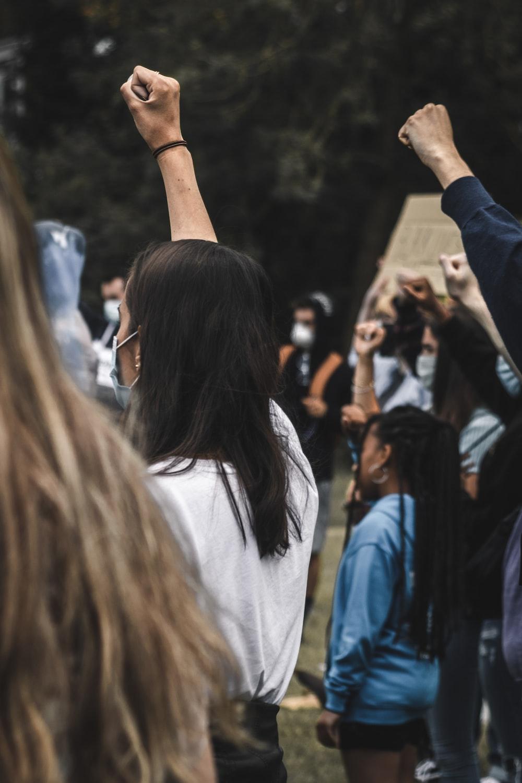 woman in white shirt raising her left hand