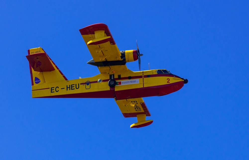 red and yellow plane flying in the sky