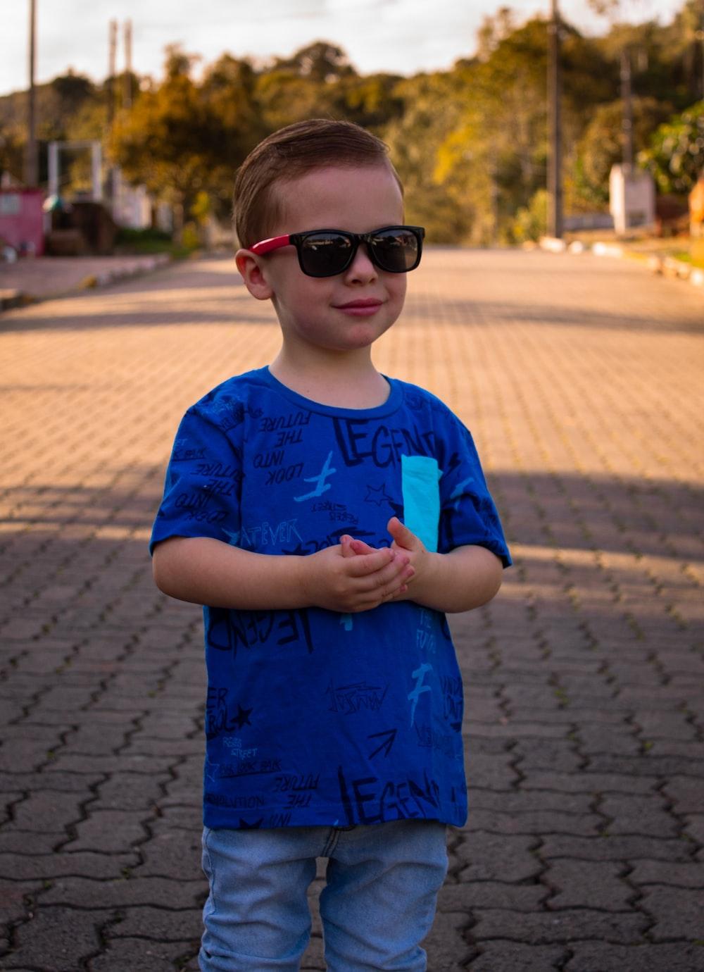 boy in blue crew neck t-shirt wearing brown sunglasses standing on sidewalk during daytime