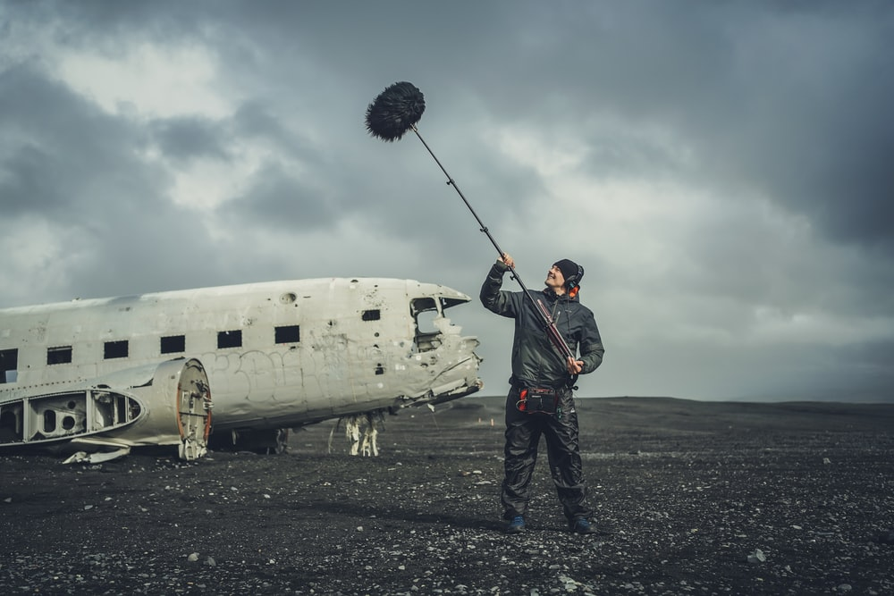 man in black jacket and black pants standing beside white airplane under cloudy sky during daytime