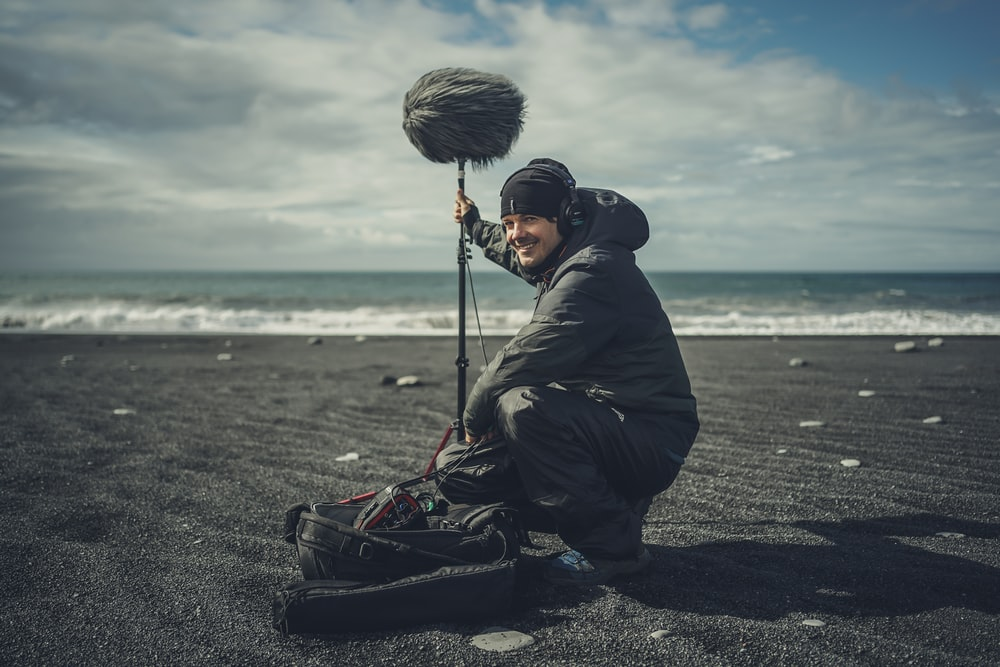 man in black jacket and black pants holding fishing rod standing on beach during daytime