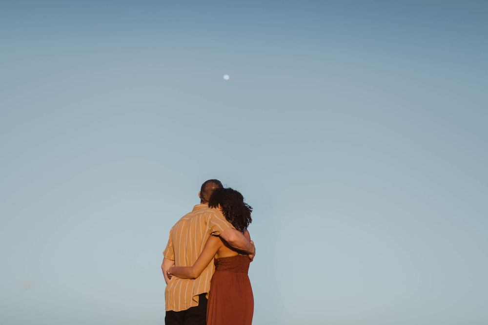 man and woman kissing under blue sky during daytime