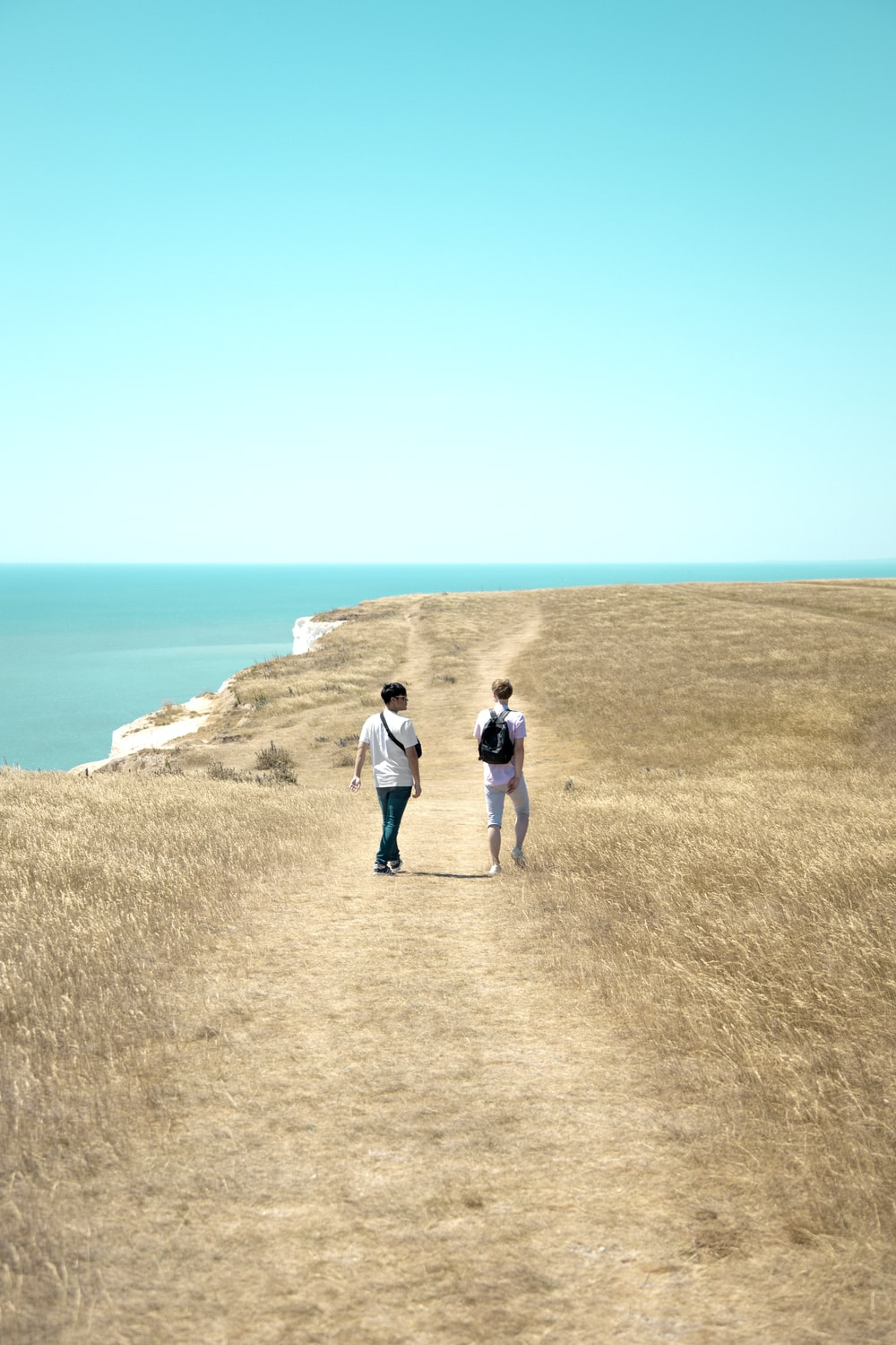 2 men and woman standing on brown rock formation near blue sea during daytime