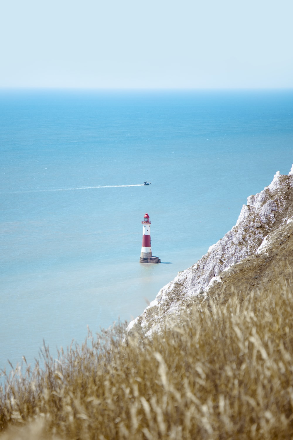 white and red lighthouse on cliff near body of water during daytime
