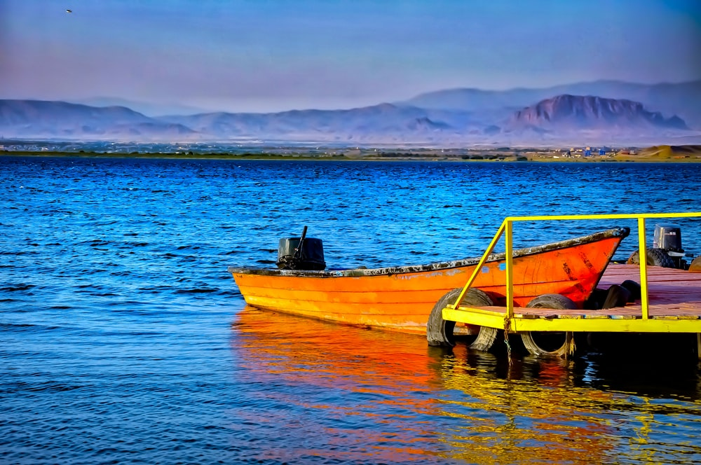 brown and green boat on body of water during daytime