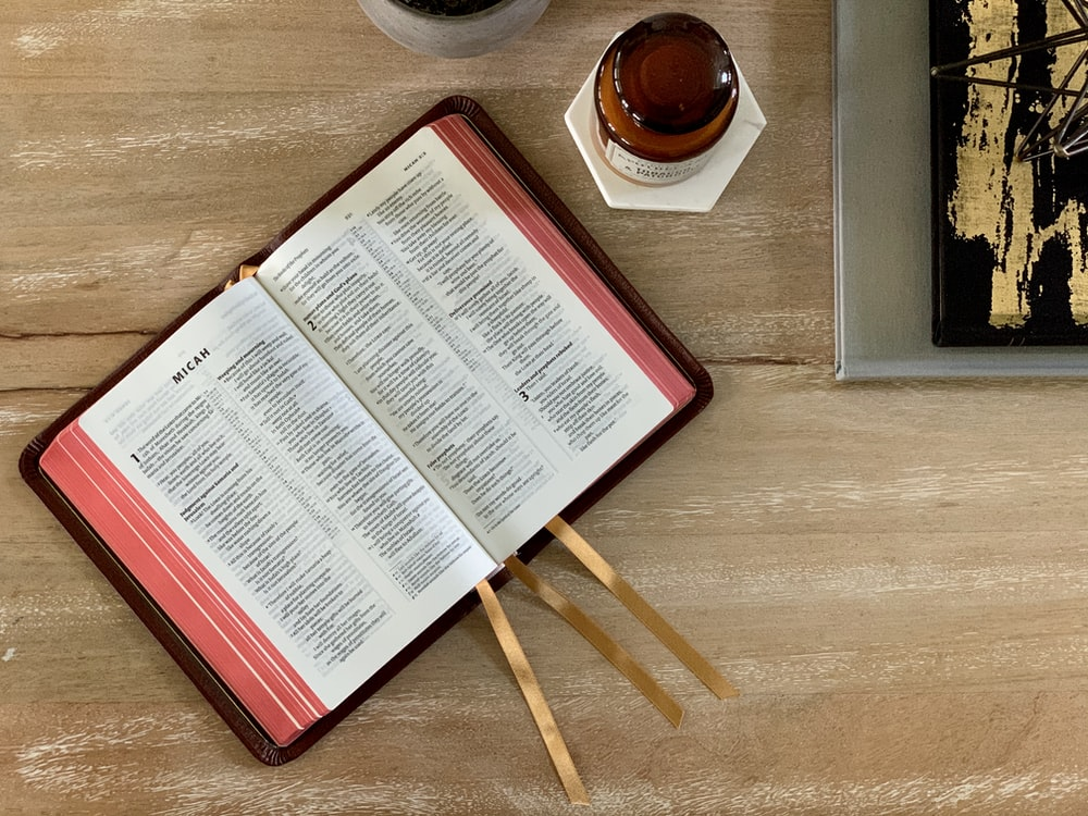 white and red book page on brown wooden table