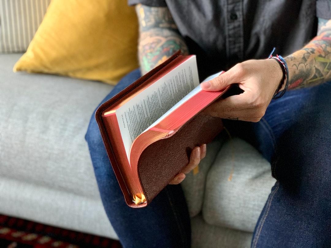A tattooed man flips through an Allan NIV Bible.