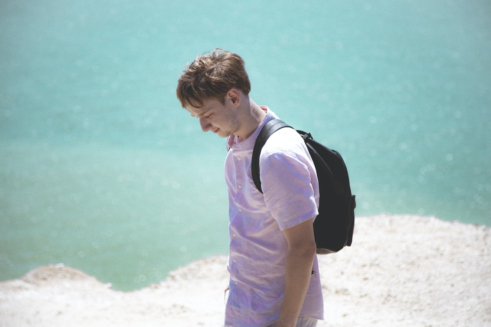 man in purple shirt and black backpack standing on beach during daytime