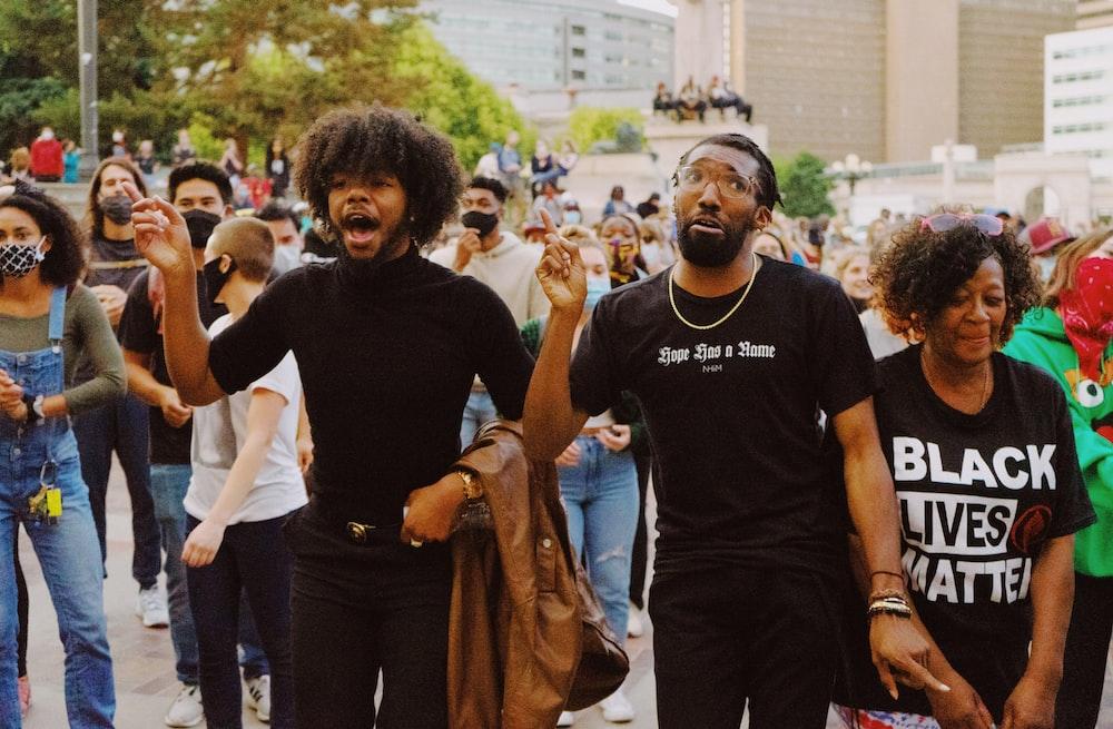 man in black crew neck t-shirt standing beside man in black crew neck t-shirt