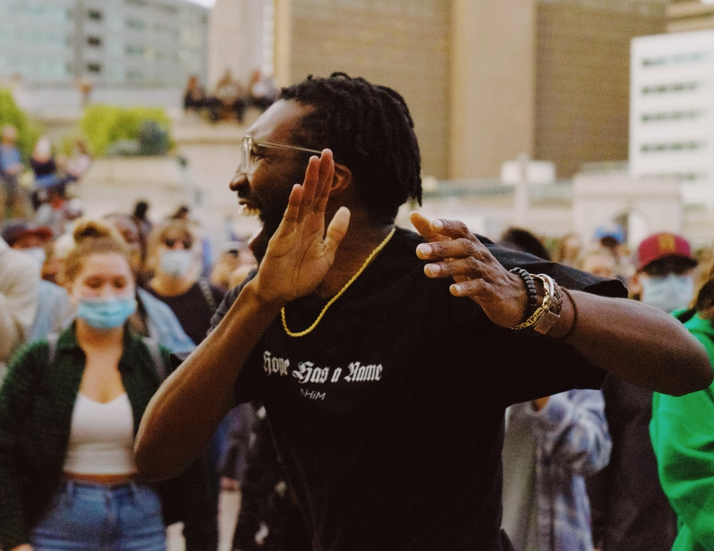 man in black crew neck t-shirt holding smartphone
