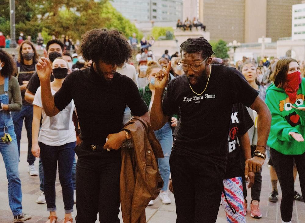 man in black crew neck t-shirt standing beside man in black t-shirt
