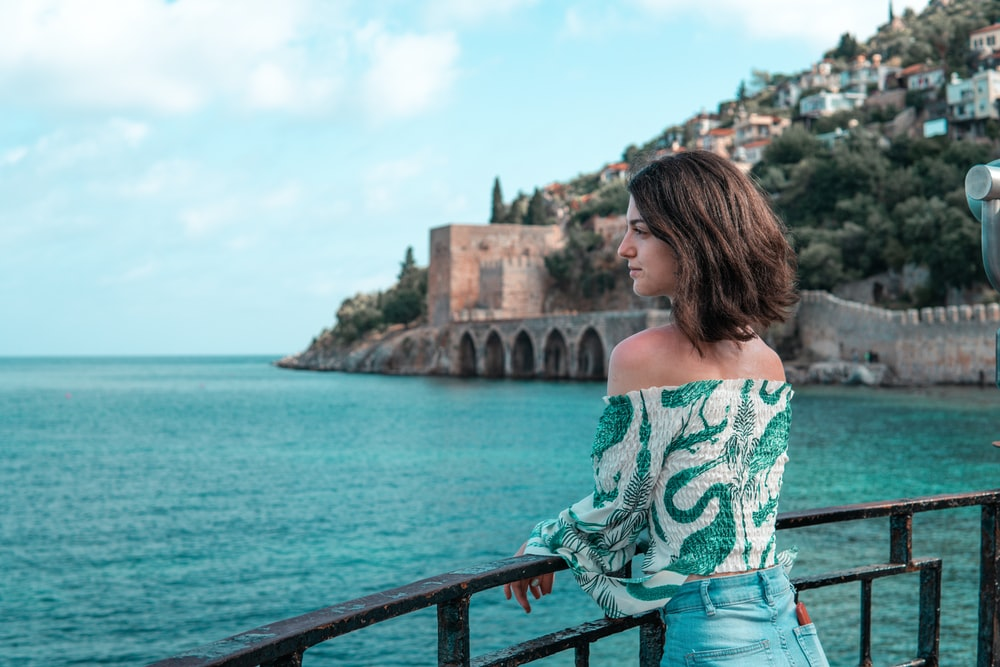 woman in green and white floral off shoulder shirt standing on bridge during daytime