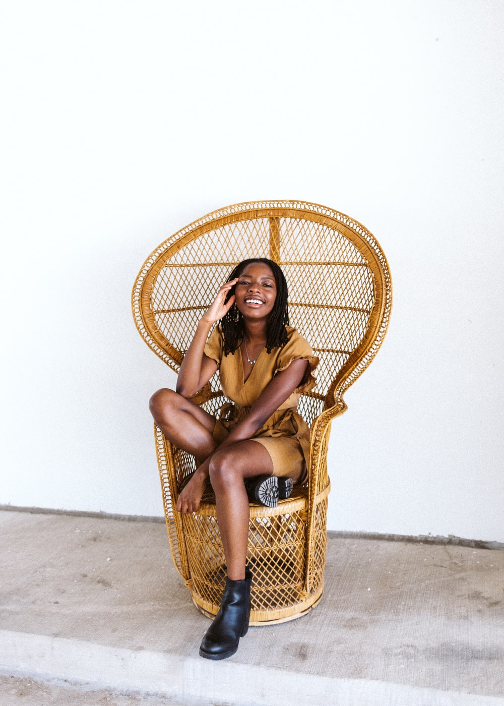 woman in brown woven hat sitting on brown woven chair