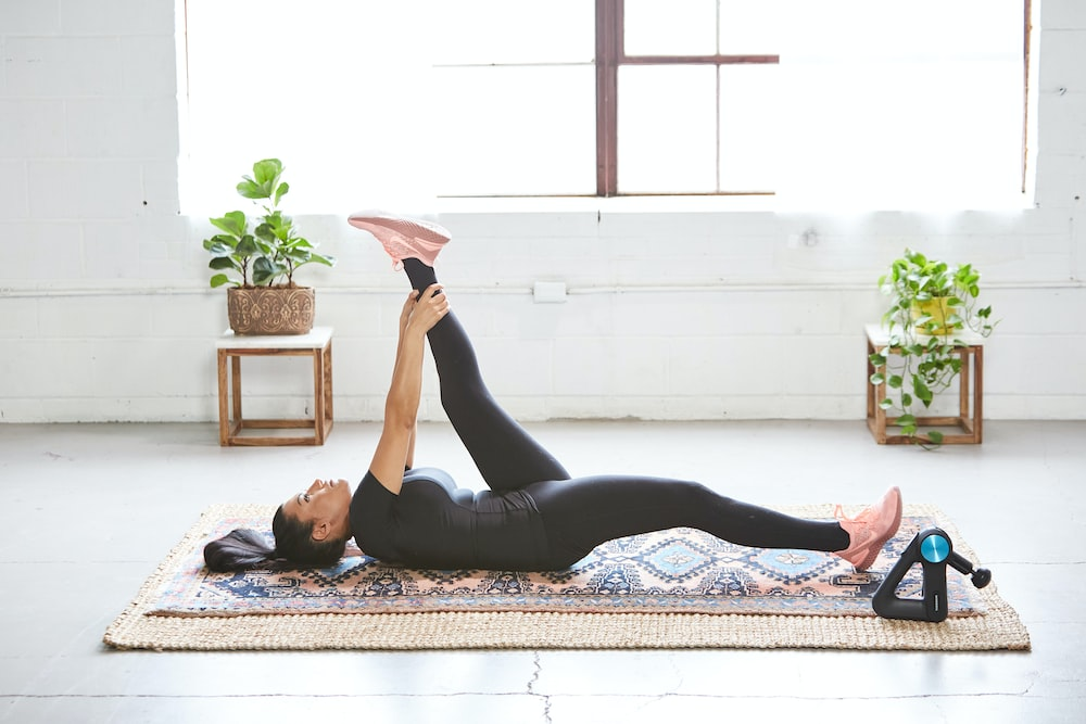 woman in black tank top and black leggings lying on black and white floral area rug