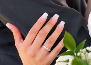 person wearing silver ring and ring