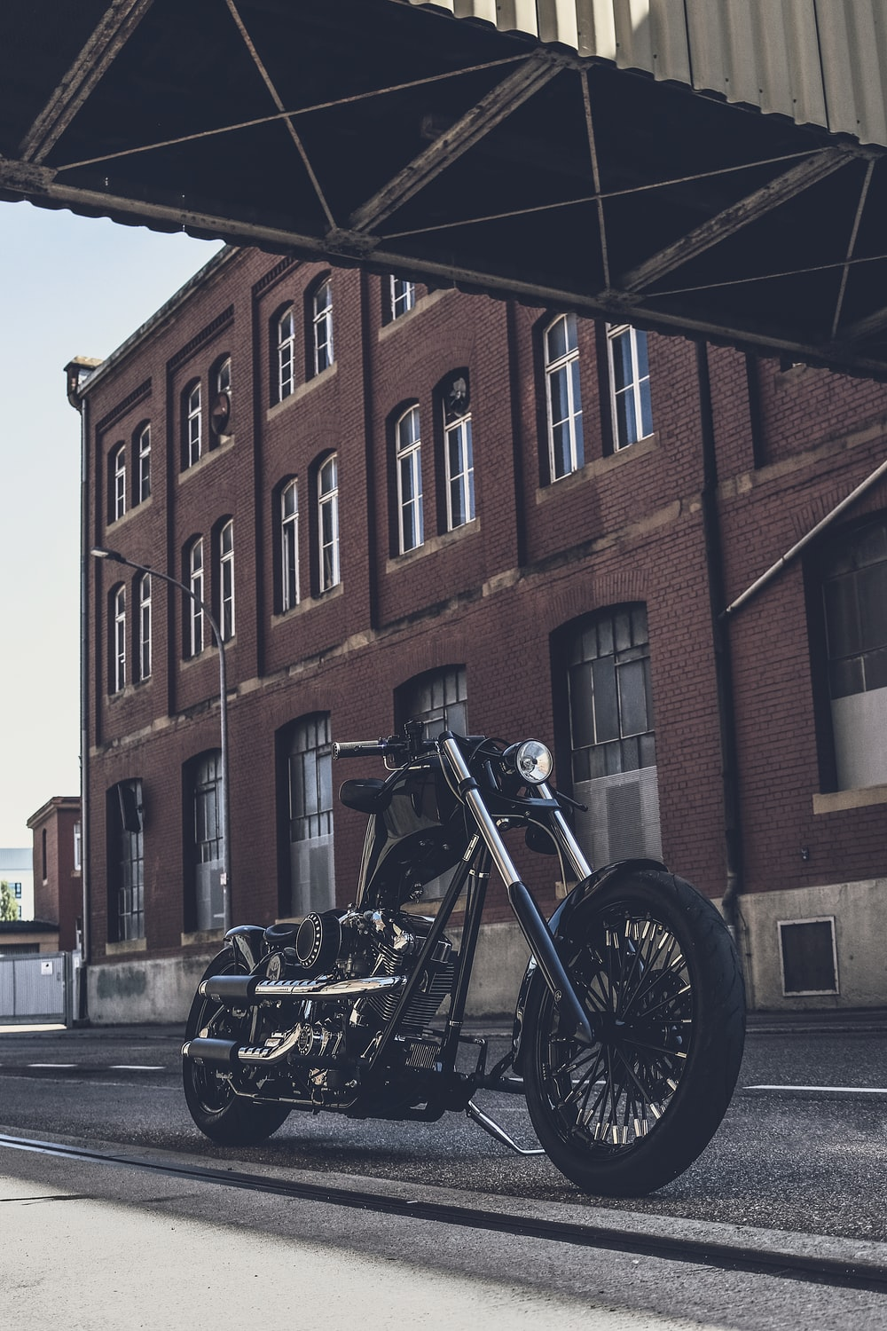 black motorcycle parked beside brown concrete building during daytime