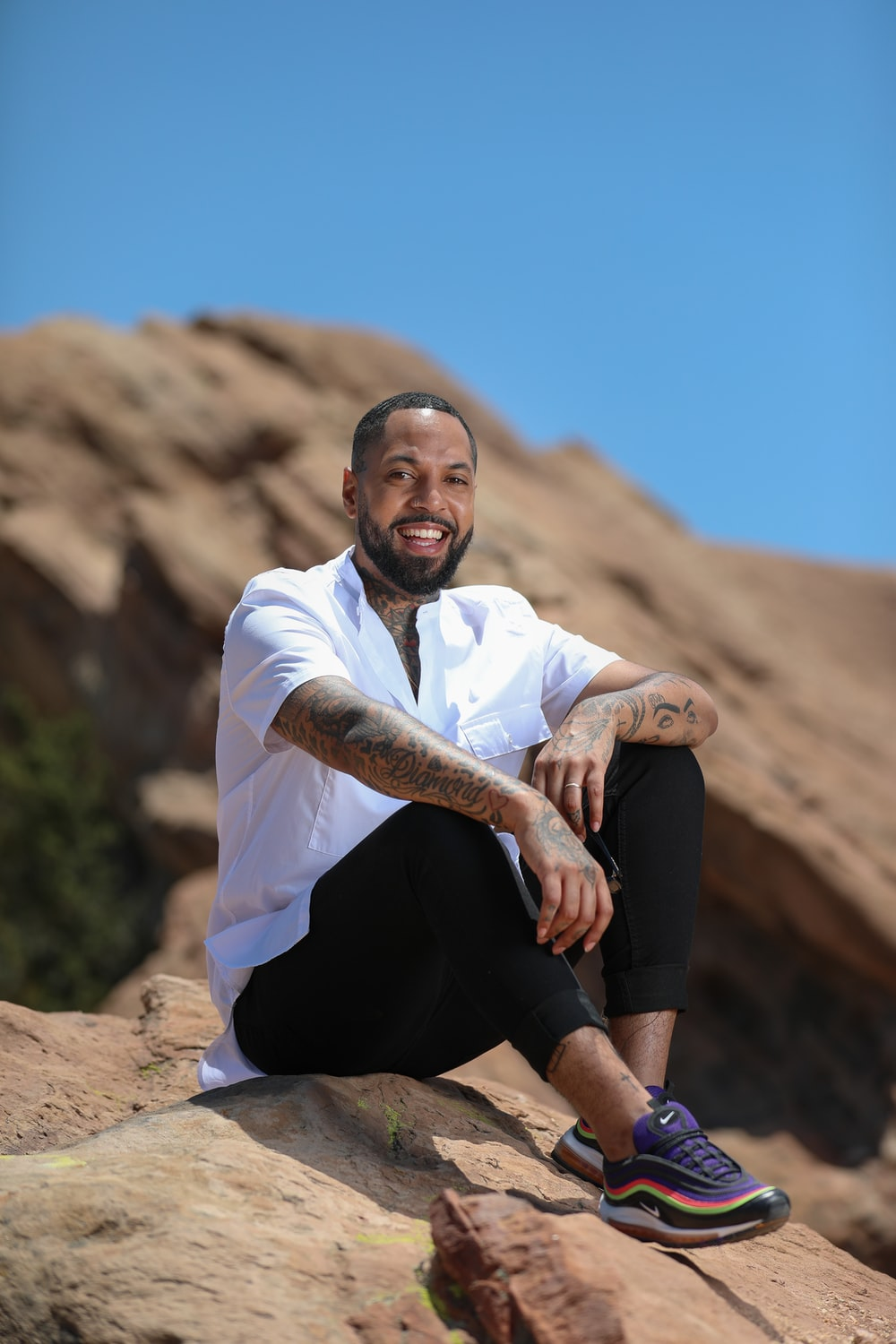 man in white button up shirt and black shorts sitting on brown rock during daytime