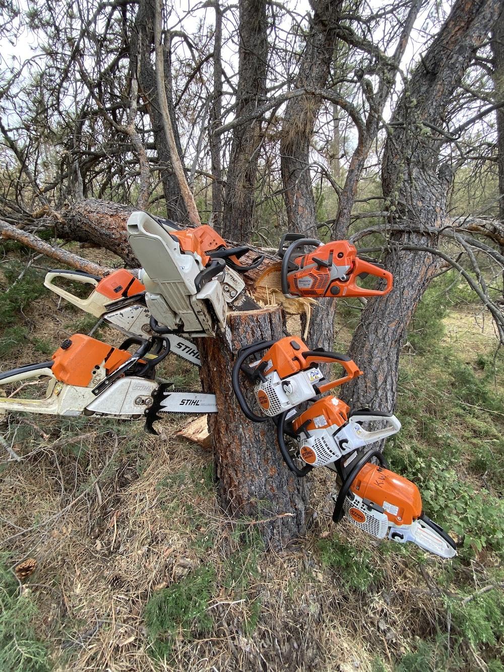 orange and white snow blower on brown tree