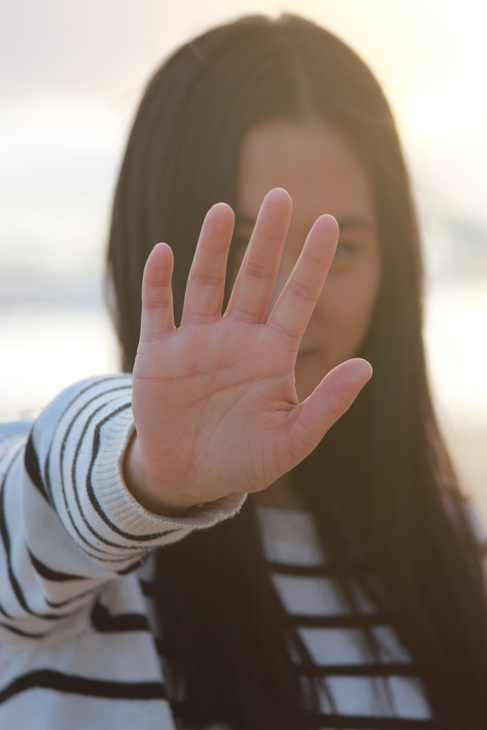 woman in white and gray striped long sleeve shirt covering her face with her hand