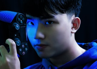 boy in blue long sleeve shirt holding black game controller