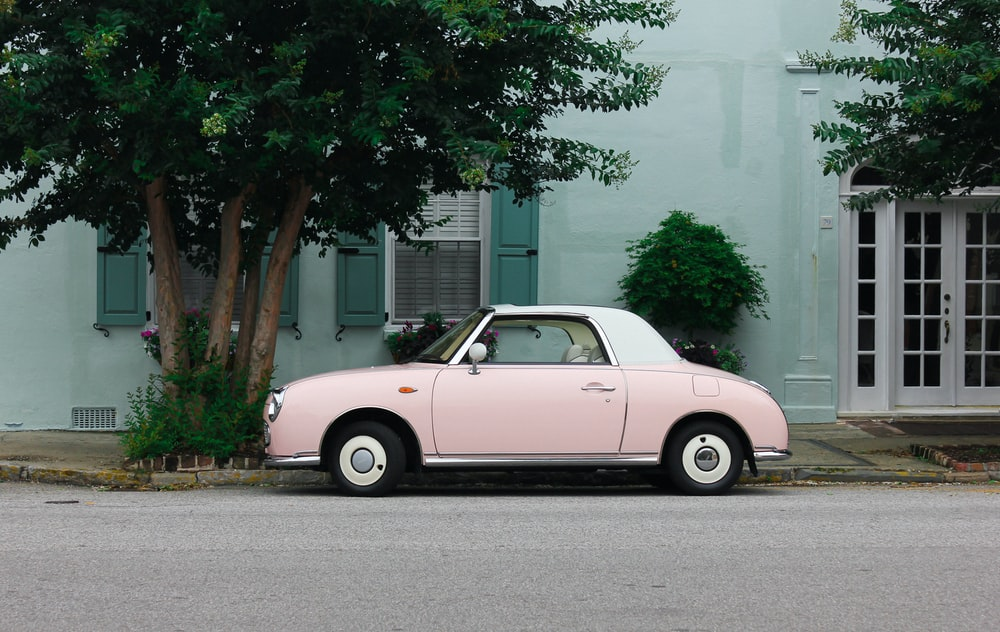 pink and white coupe parked beside green trees during daytime