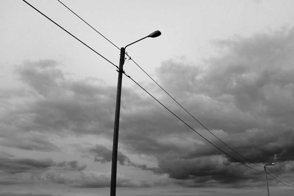 grayscale photo of street light under cloudy sky