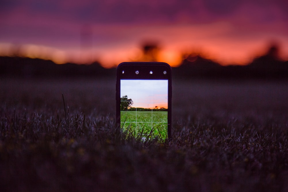 black iphone 5 on green grass during sunset