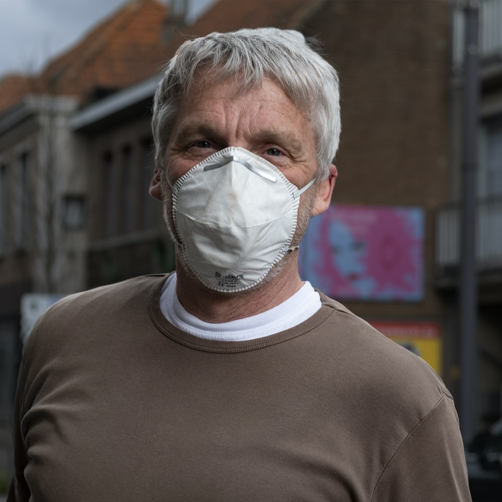 man in gray crew neck shirt with white face mask