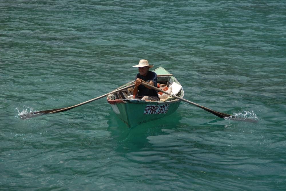 man in white shirt riding on boat during daytime