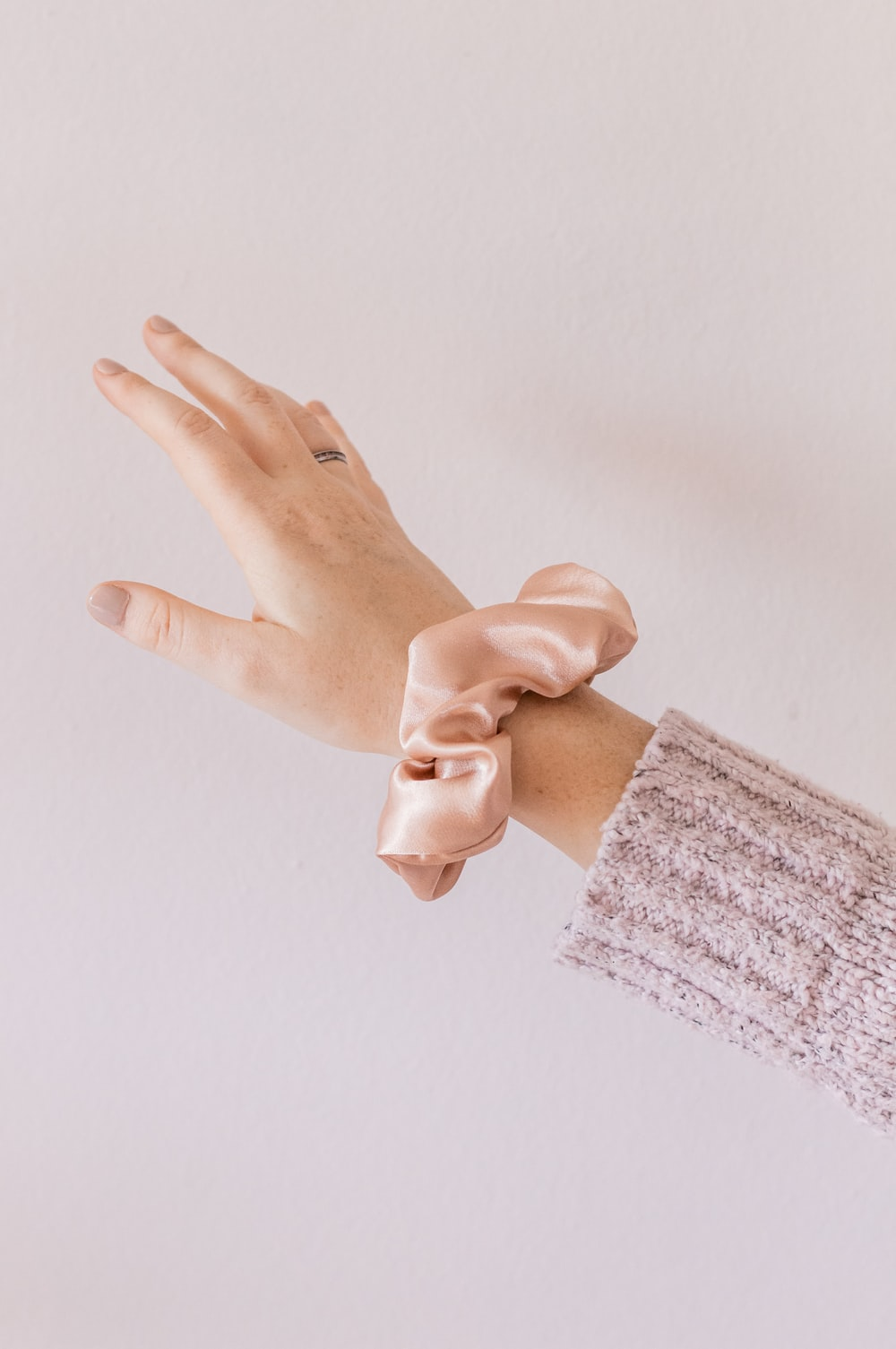 person holding hands with pink manicure
