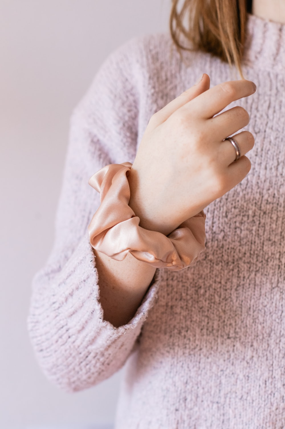 woman in white knit sweater holding her hand