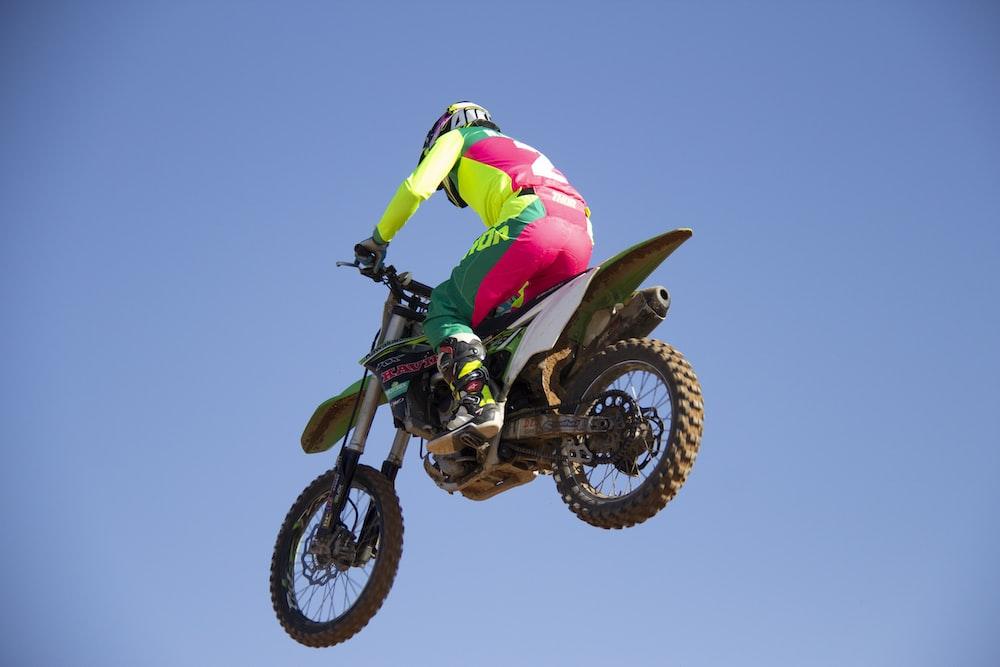 man in green and black motocross suit riding motocross dirt bike