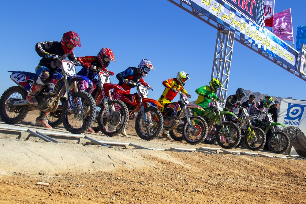 people riding motocross dirt bikes during daytime