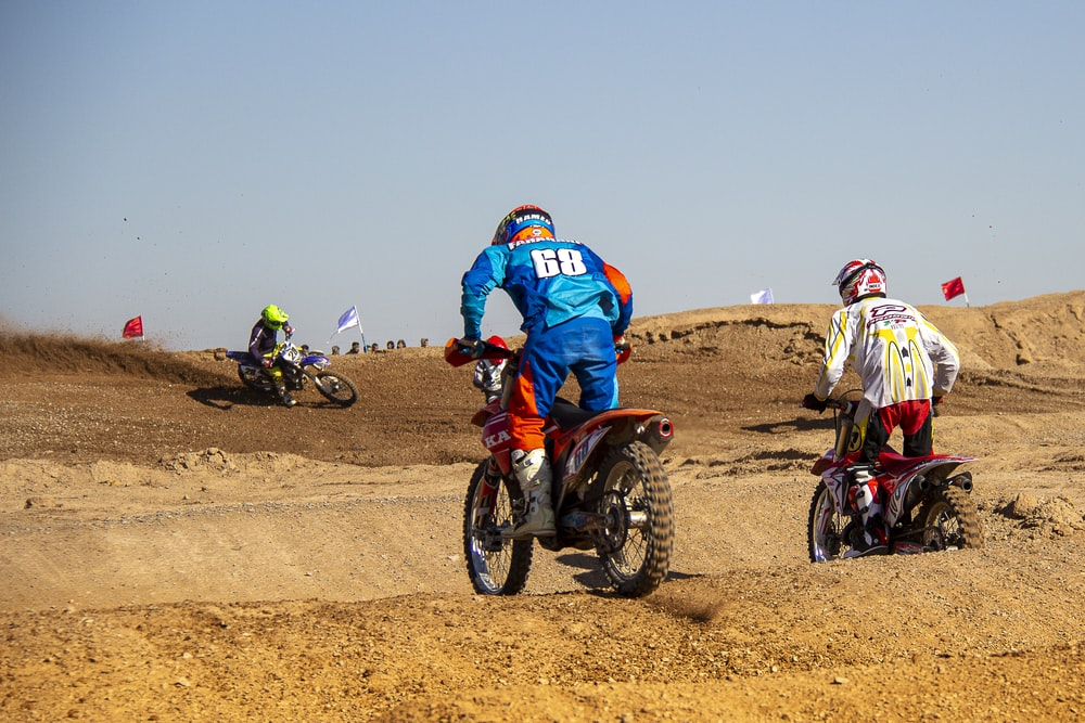 people riding motocross dirt bikes on brown sand during daytime