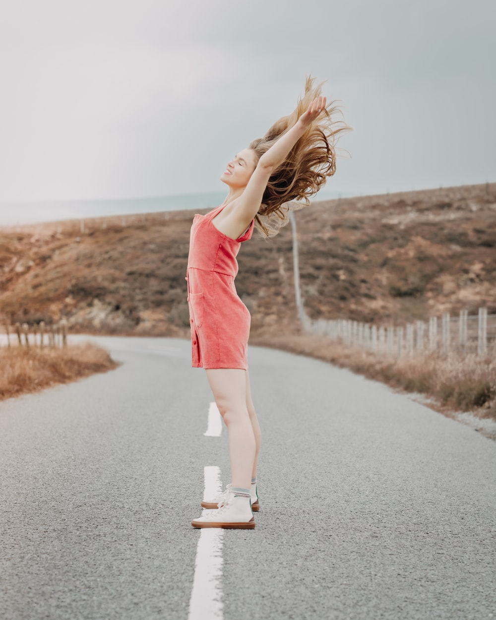 woman in red dress standing on road during daytime