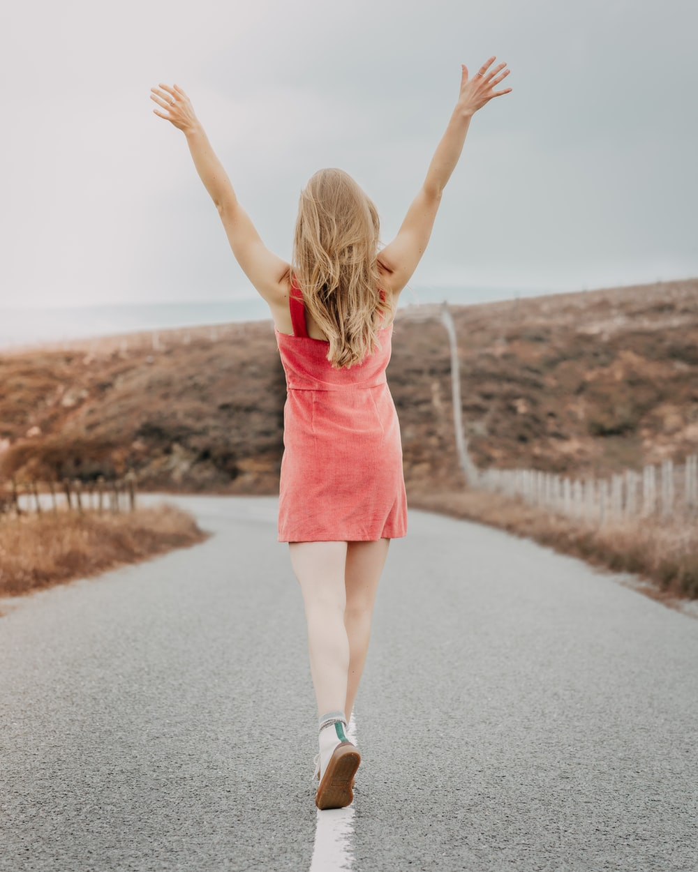 girl in pink dress standing on road during daytime
