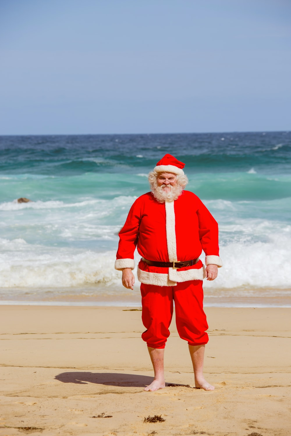man in red santa claus costume standing on beach shore during daytime