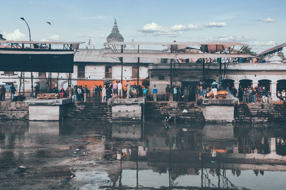 people walking on dock near white concrete building during daytime