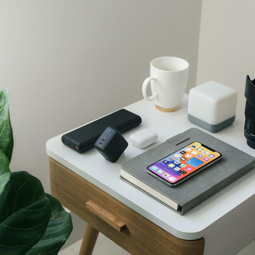 black iphone 4 beside white ceramic mug on white table